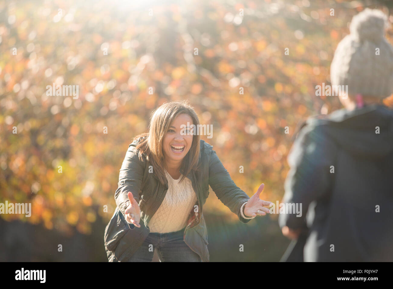 Enthusiastic mother reaching for son in autumn park - Stock Image