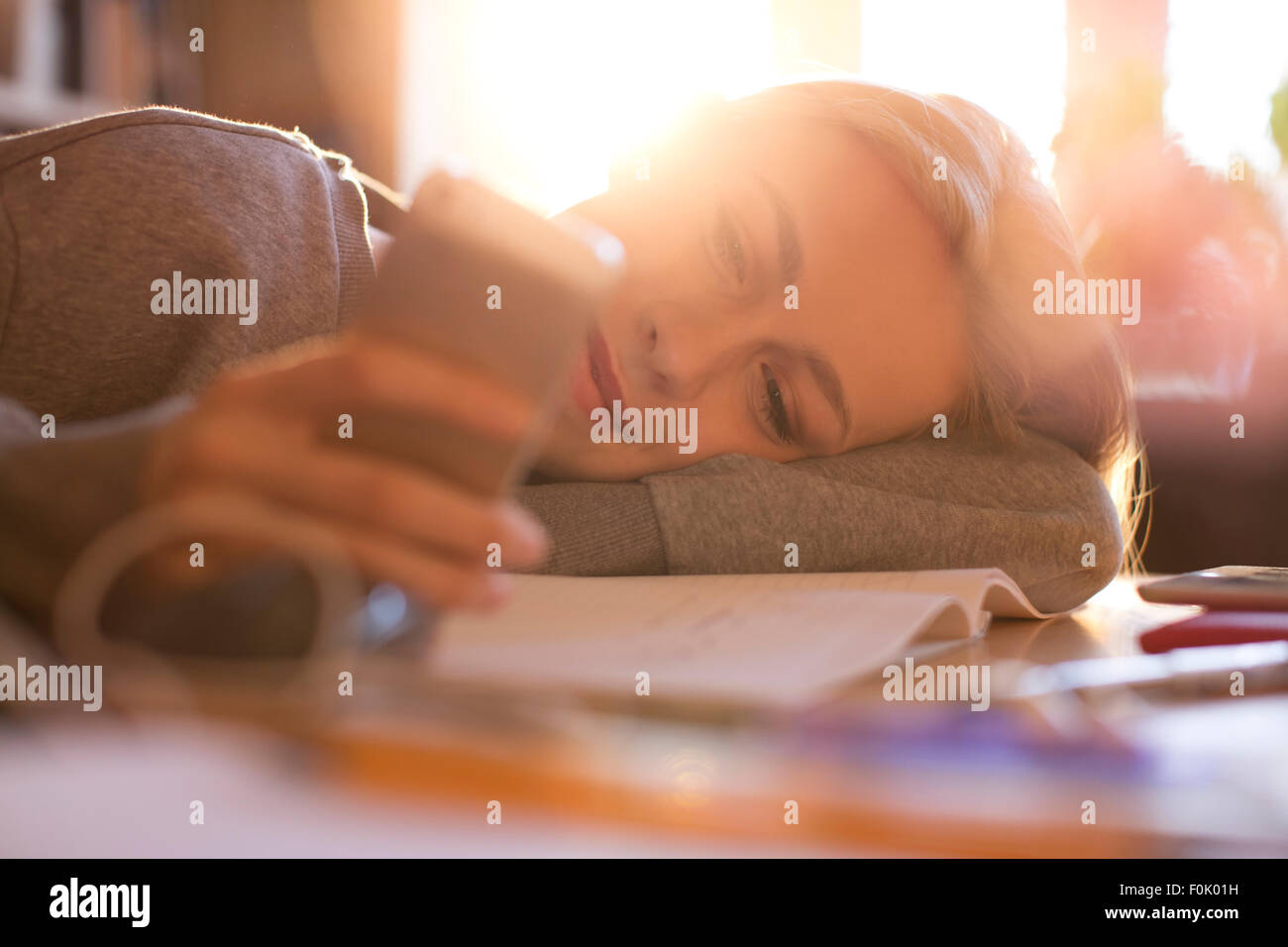 Teenage girl laying and texting with cell phone - Stock Image