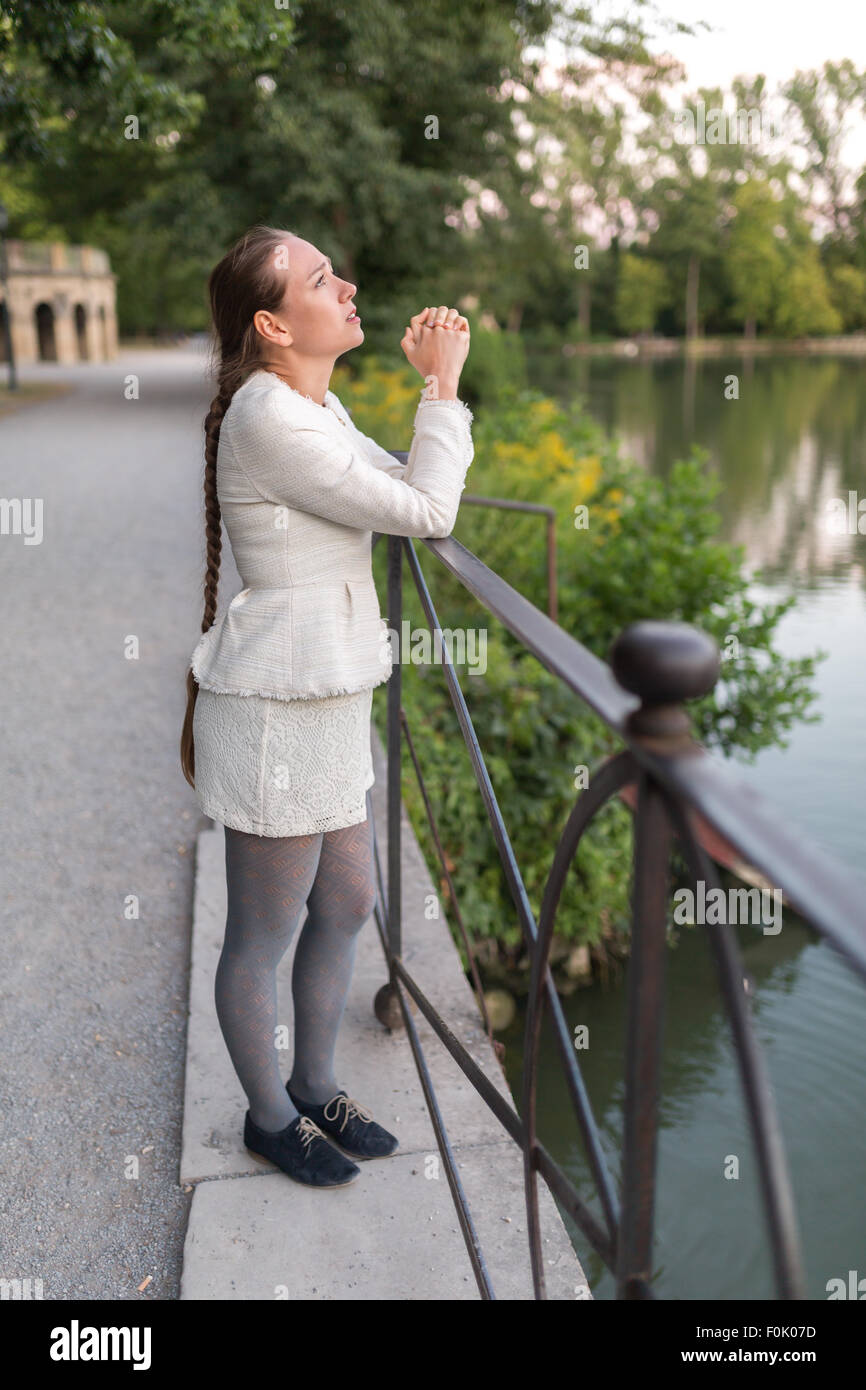 Young woman praying at the harbor while looking to the sky - Stock Image