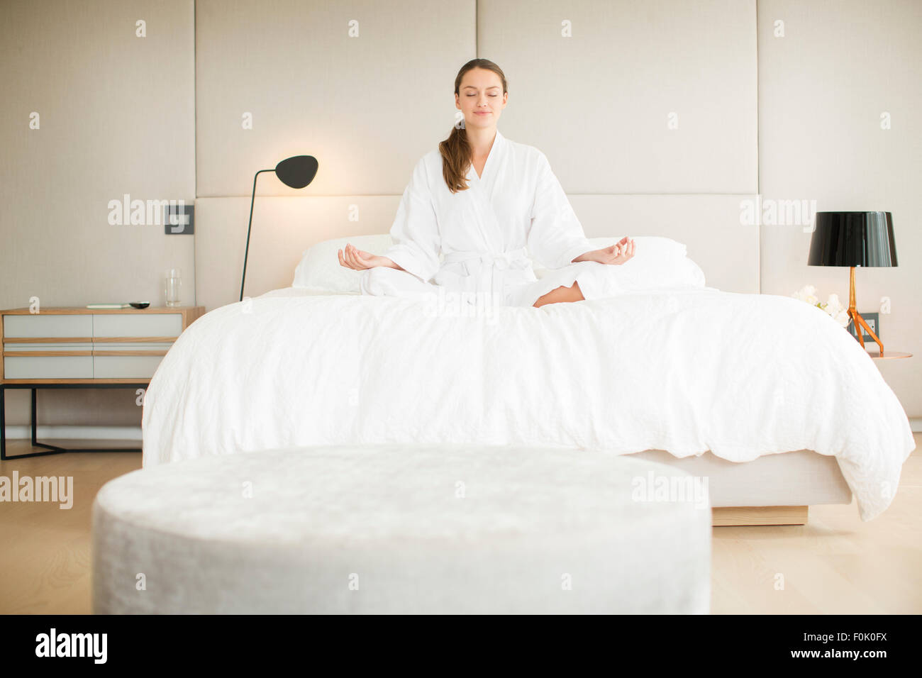 Serene woman in bathrobe meditating in lotus position on bed - Stock Image