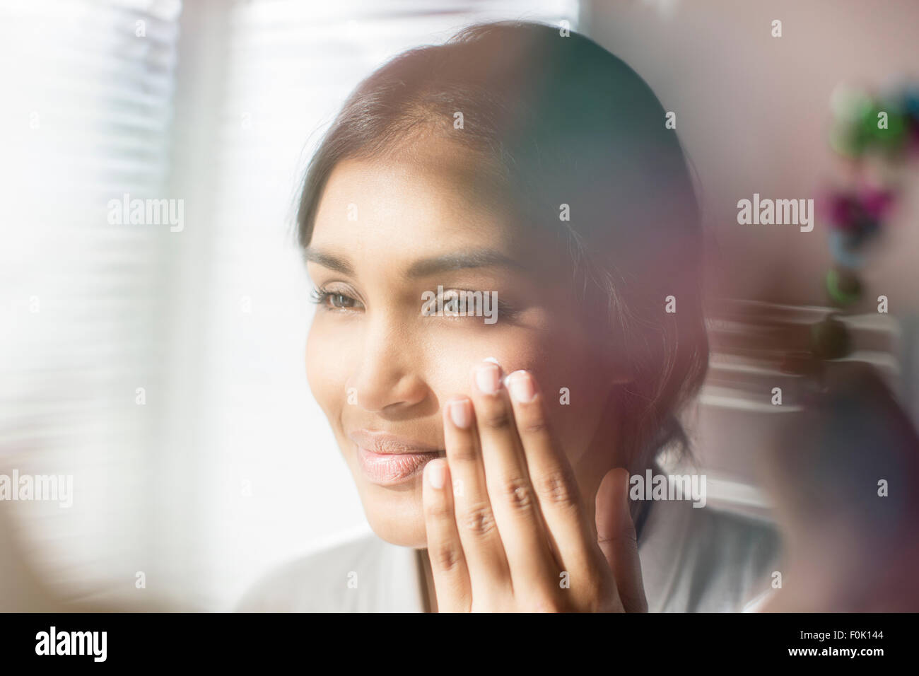 Close up woman applying moisturizer to face - Stock Image