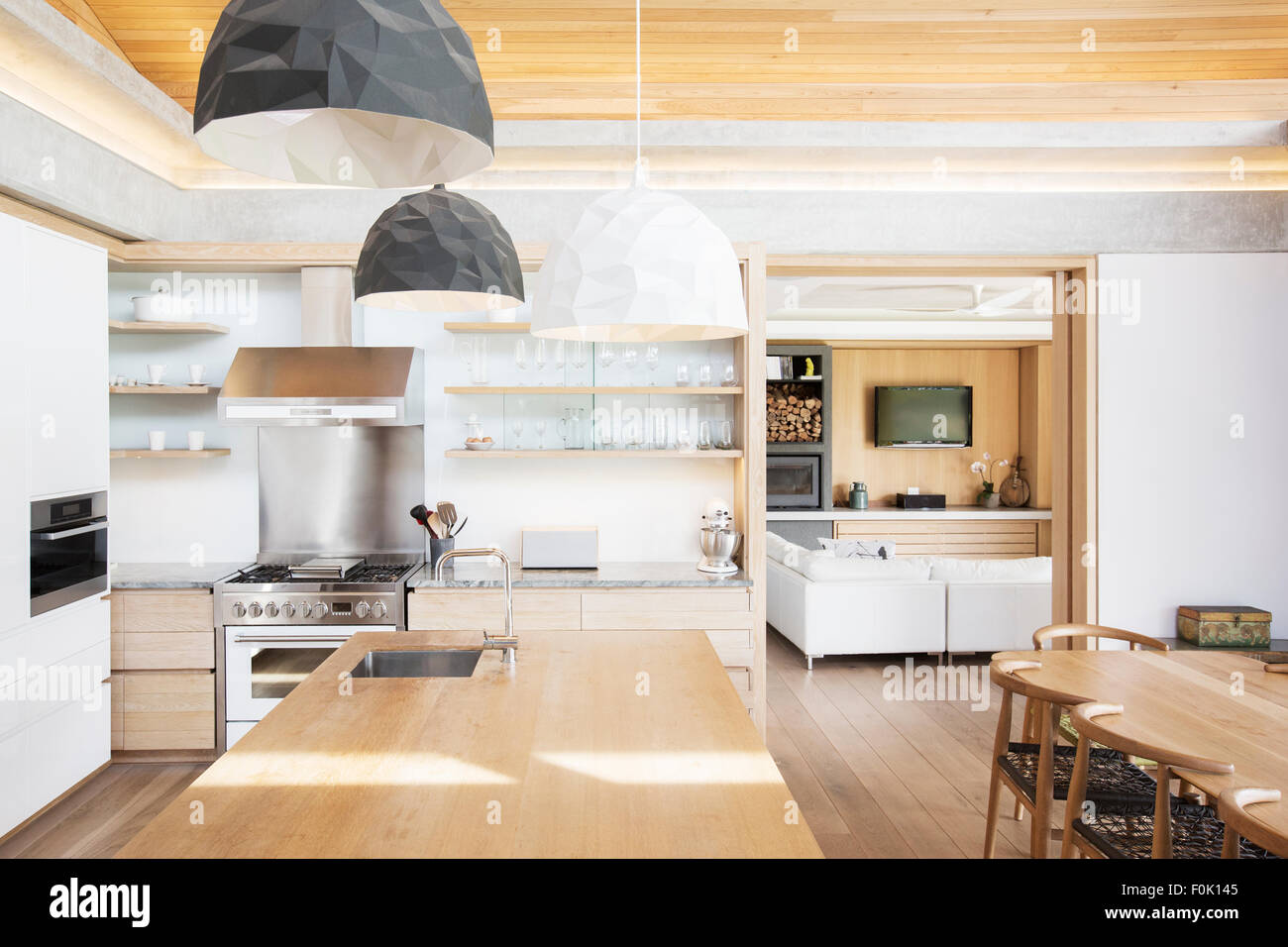 Modern pendant lights over wood kitchen island Stock Photo: 86469829 ...