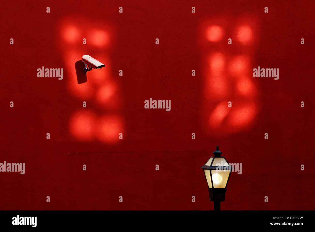 Urban alley behind shops. Red wall, security camera, streetlight and window reflection. - Stock Image