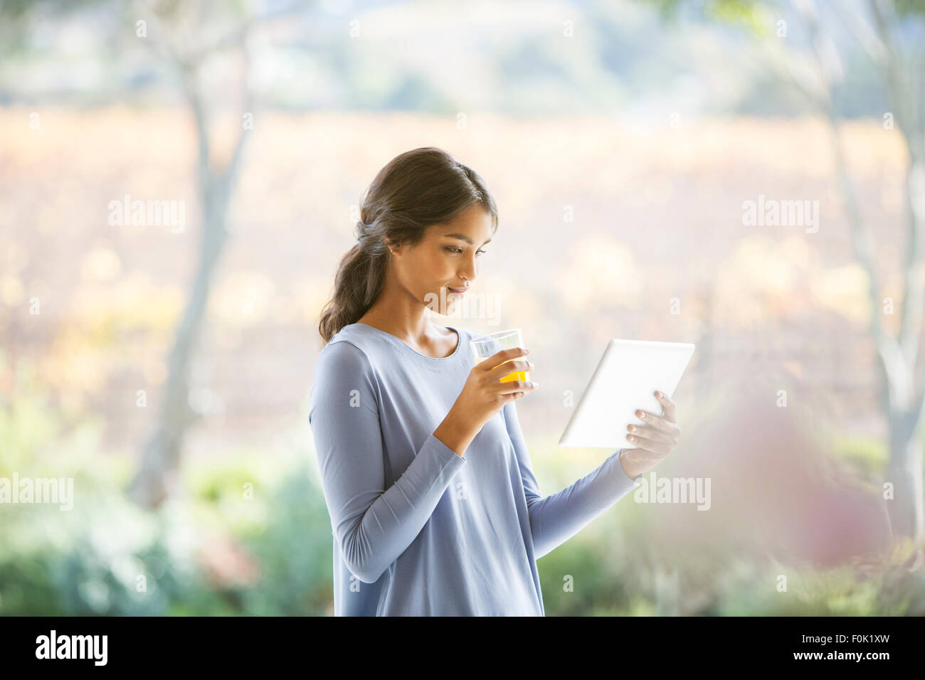 Woman drinking orange juice and using digital tablet - Stock Image