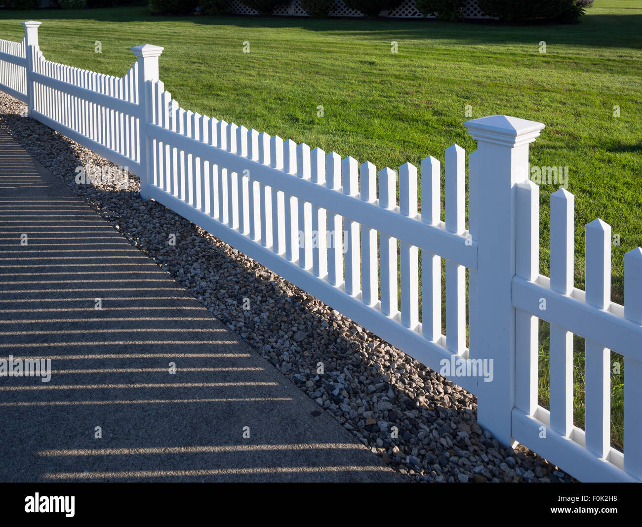 White picket fence that delineates the grass from the pathway - Stock Image