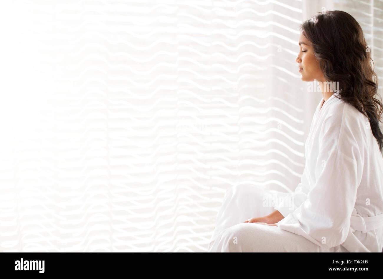 Serene woman in bathrobe meditating at sunny window - Stock Image