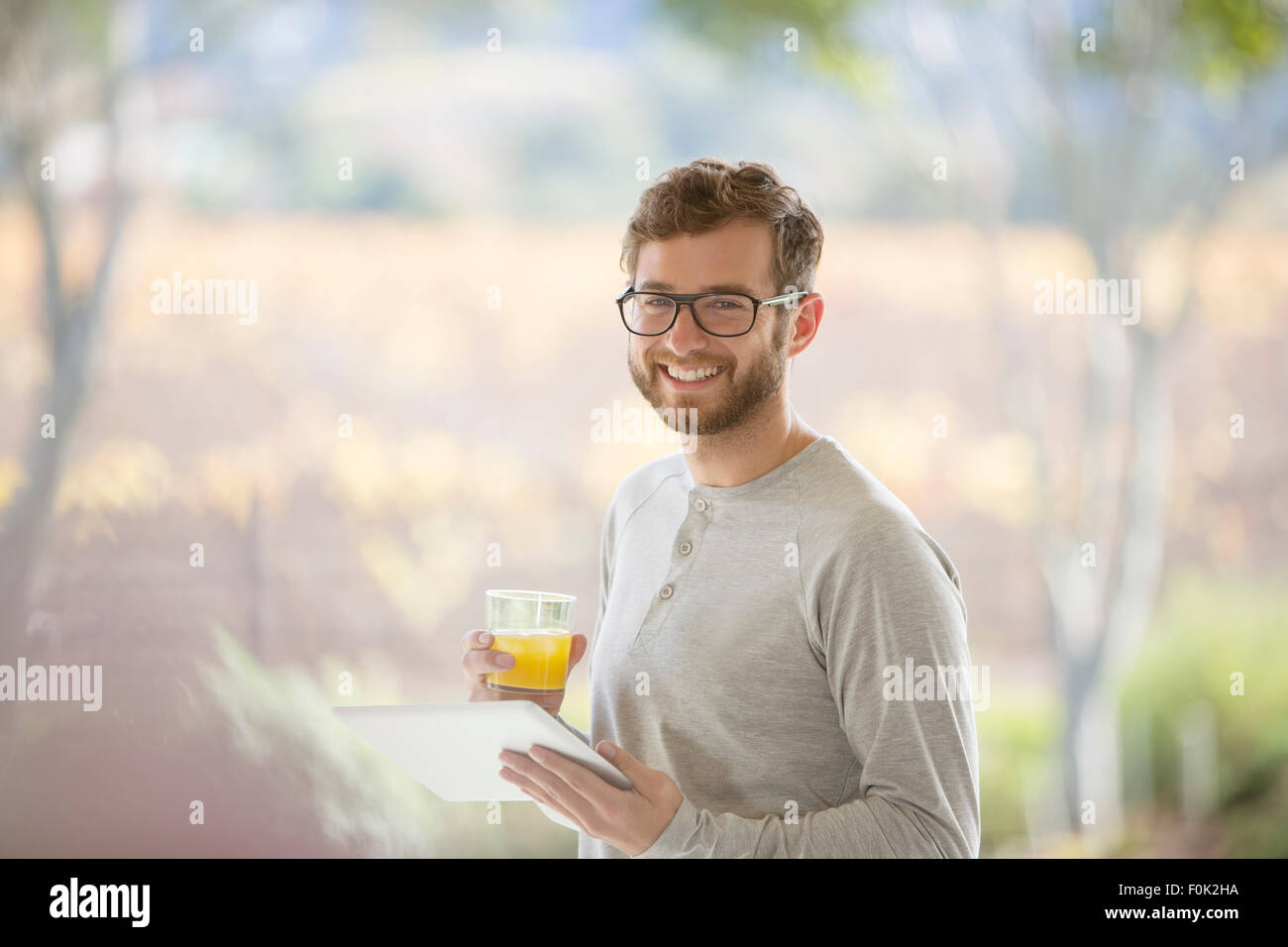 Portrait smiling man drinking orange juice and using digital tablet on patio - Stock Image