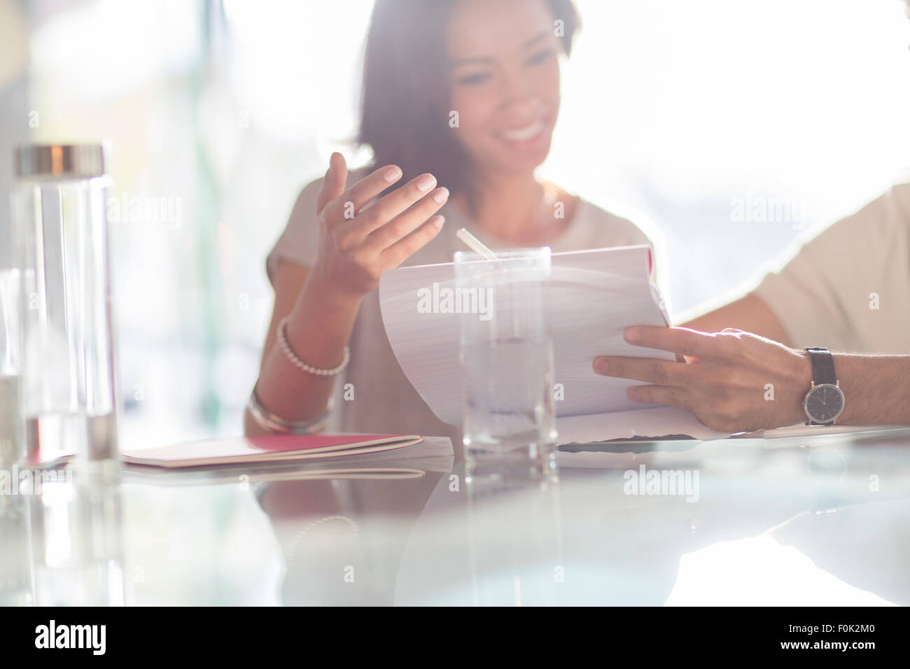 Businesswoman gesturing to paperwork in meeting - Stock Image