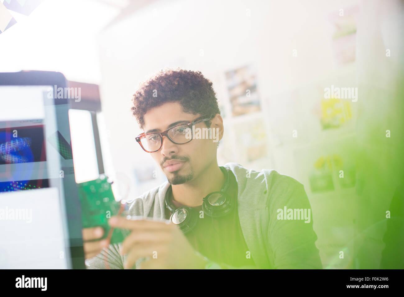Creative designer with headphones examining part in office - Stock Image