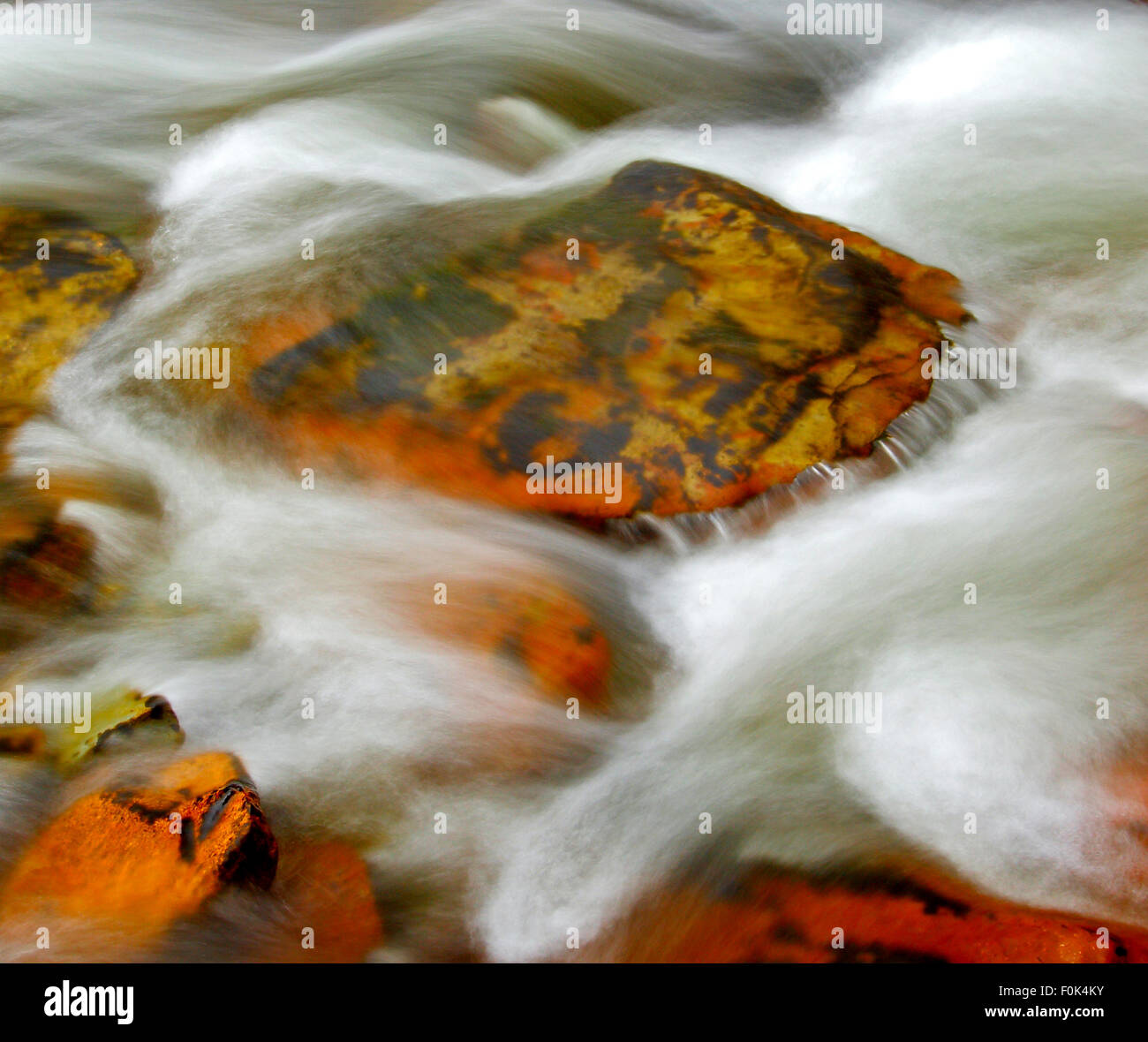 Long exposure of swiftly moving stream with white water and rocks. - Stock Image