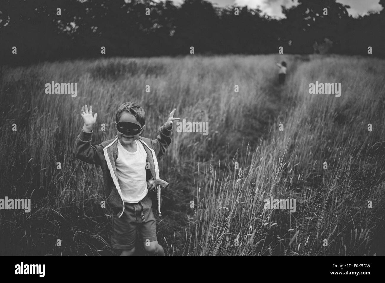 A young boy in a mask with a toy gun in a field - Stock Image