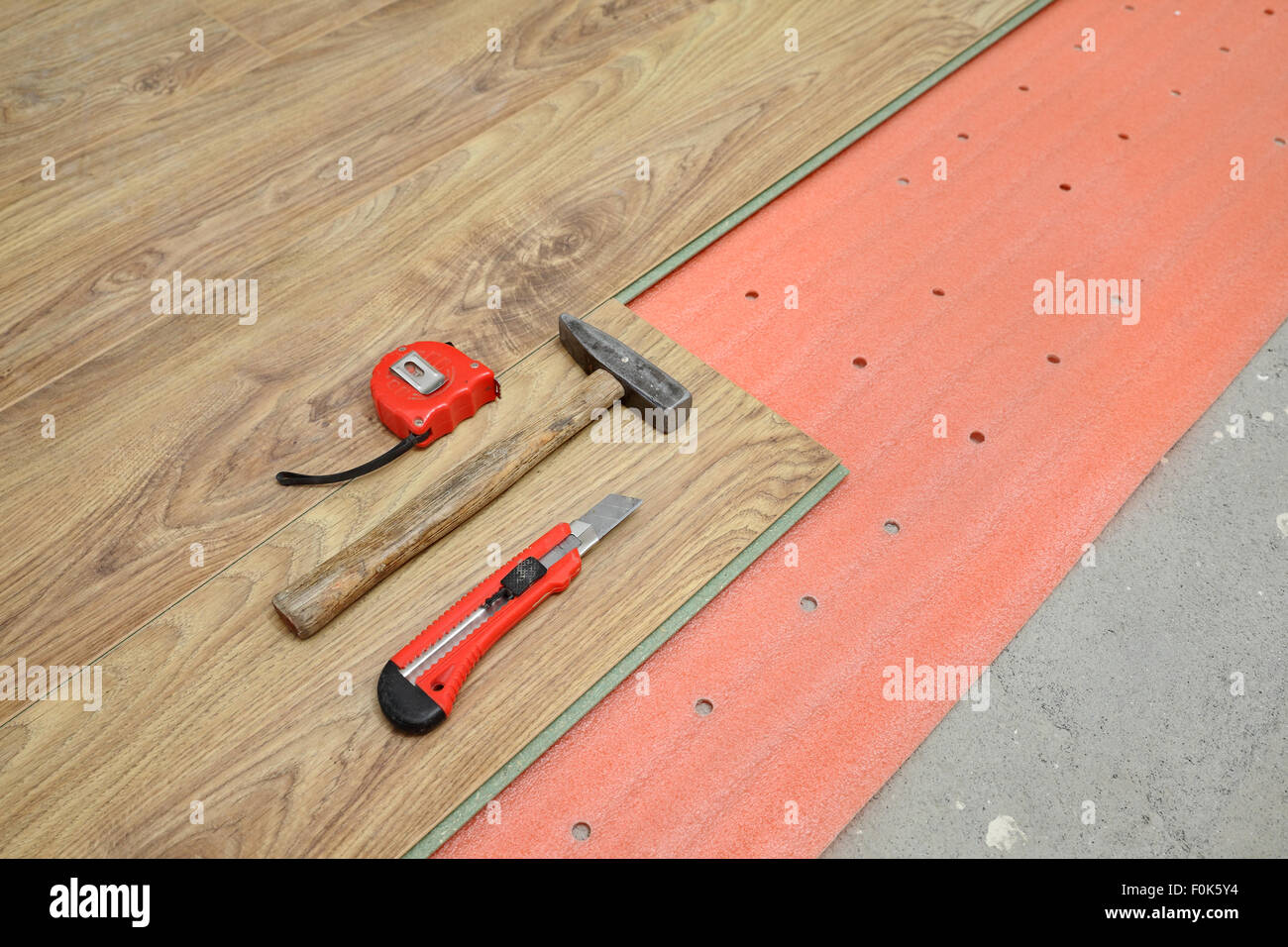 Flooring of room, laminate, foam and tools, hammer, meter, cutter - Stock Image