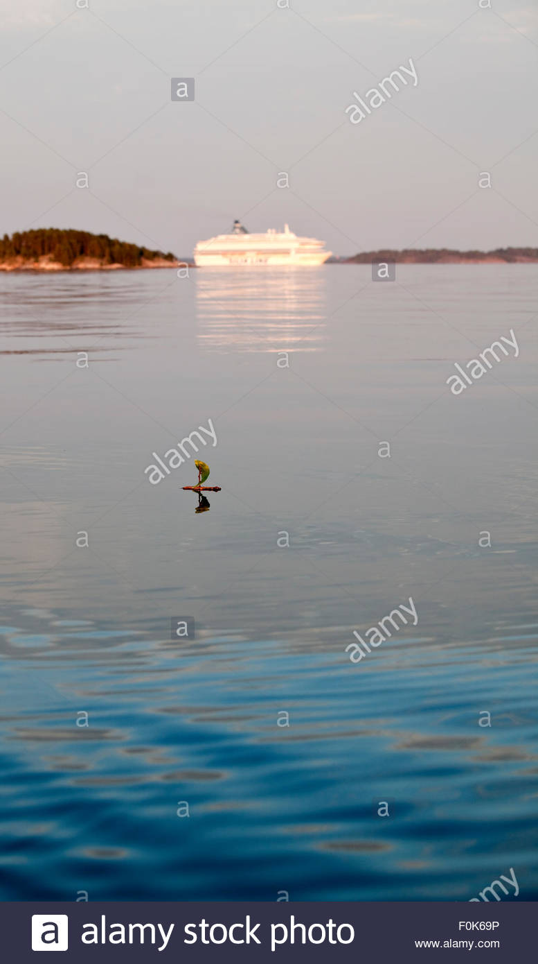 Small toy boat and big ferry on the same sea - Stock Image