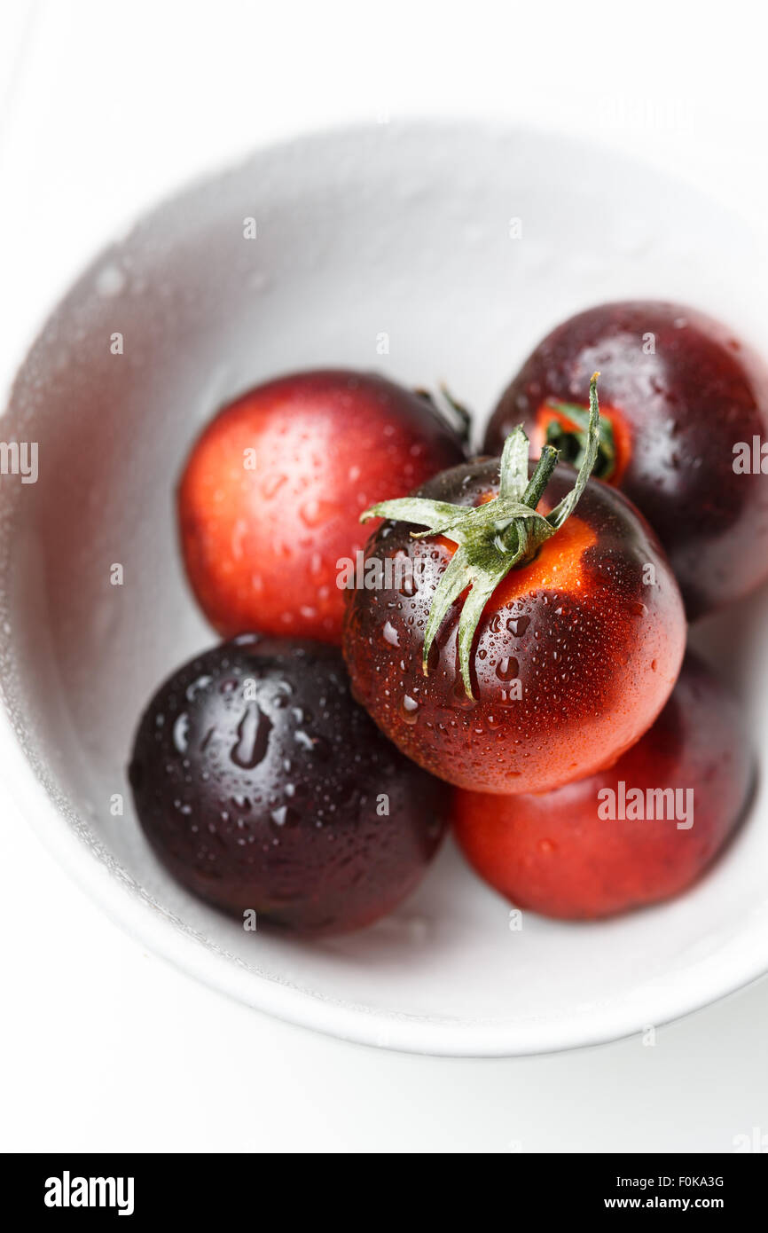 Black tomatoes in a white bowl Stock Photo