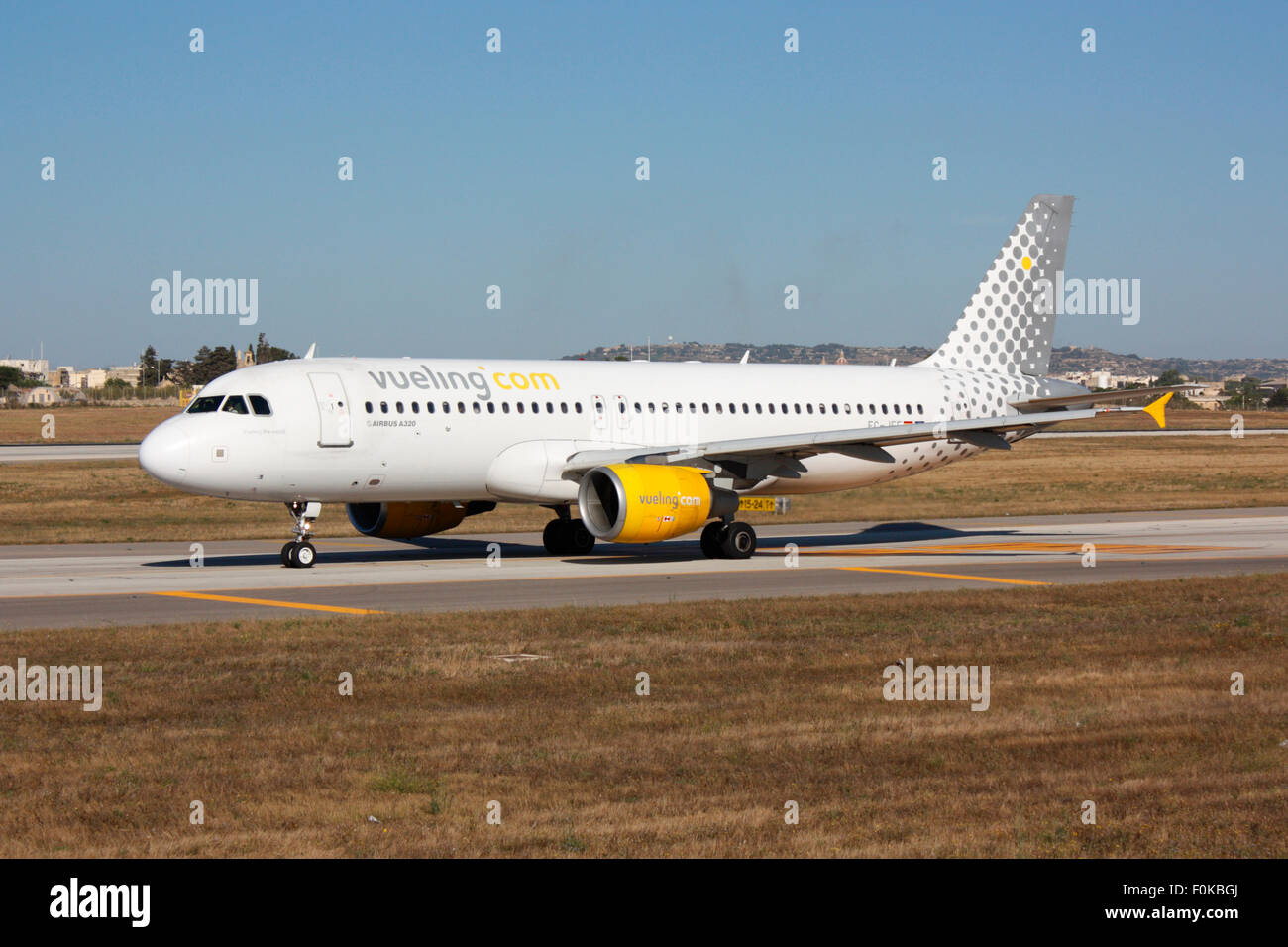 Airbus A320 jet plane belonging to the Spanish low cost airline Vueling, shown taxiing for departure from Malta - Stock Image