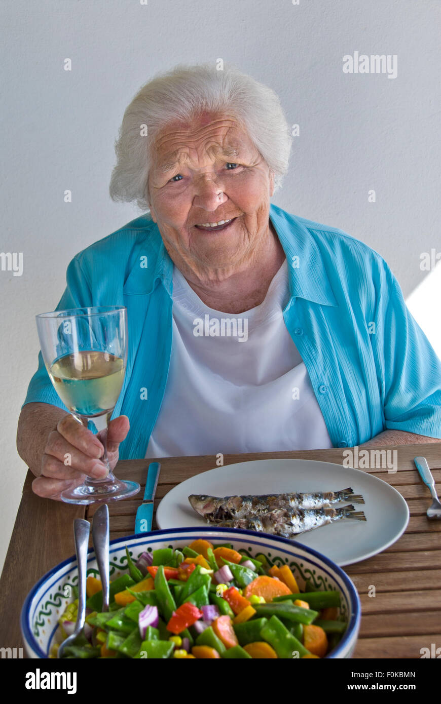 Happy elderly lady 90s on holiday enjoying healthy alfresco meal of fresh grilled fish, mixed bean salad and glass - Stock Image