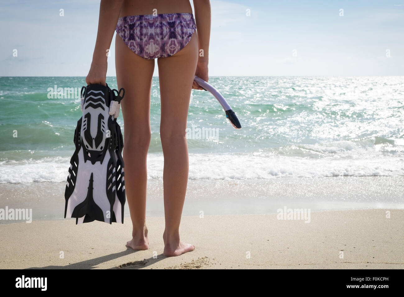 Mexico, Nayarit, teenage girl with snorkel and fins standing in front of the ocean - Stock Image
