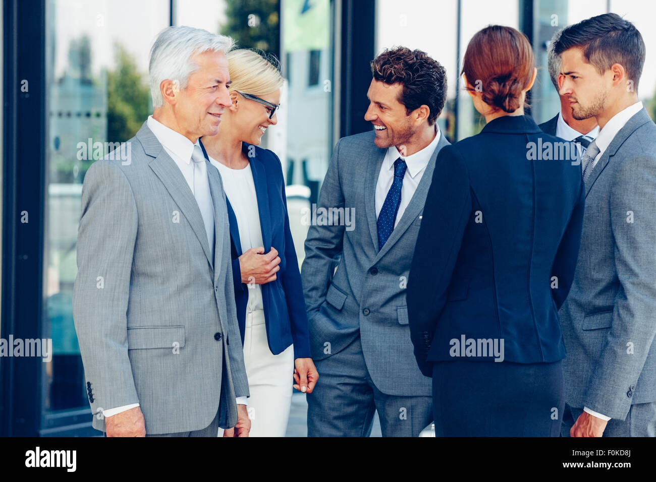Group of confident business people talking - Stock Image