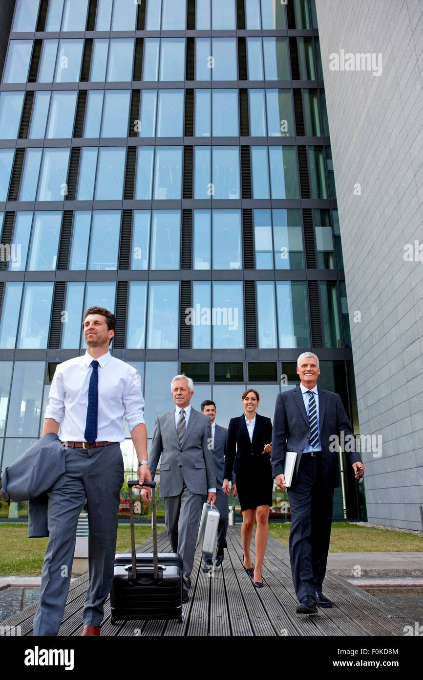 Team of business professionals walking out of office building with luggage Stock Photo