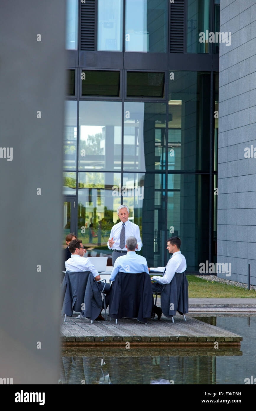 Manager talking to staff sitting on chairs outside office building - Stock Image
