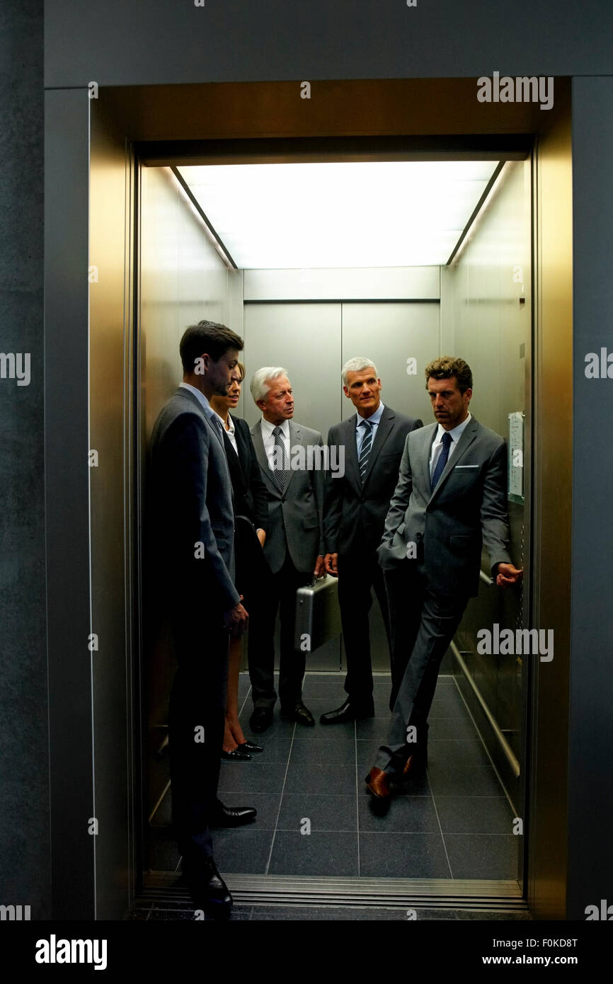 Group of businesspeople in an elevator - Stock Image