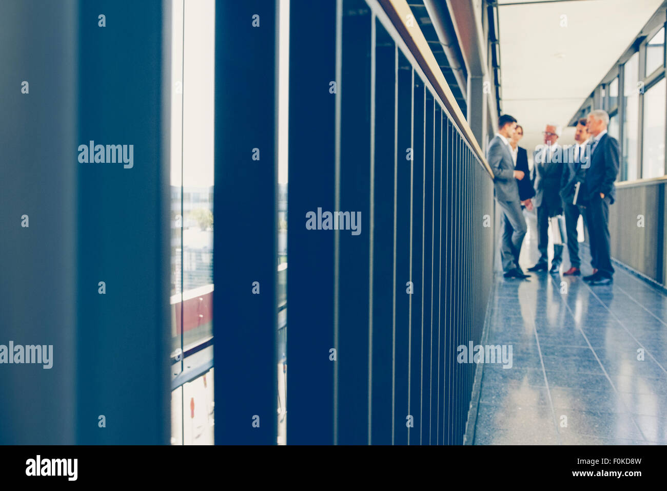 Group of business people standing on office corridor - Stock Image