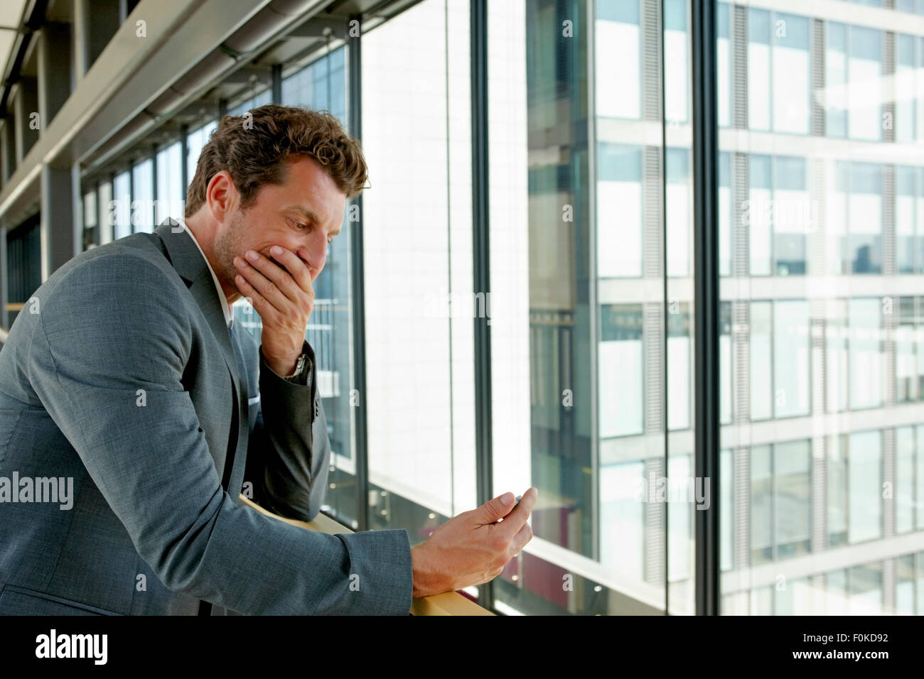 Terrified businessman reading text message on cell phone - Stock Image