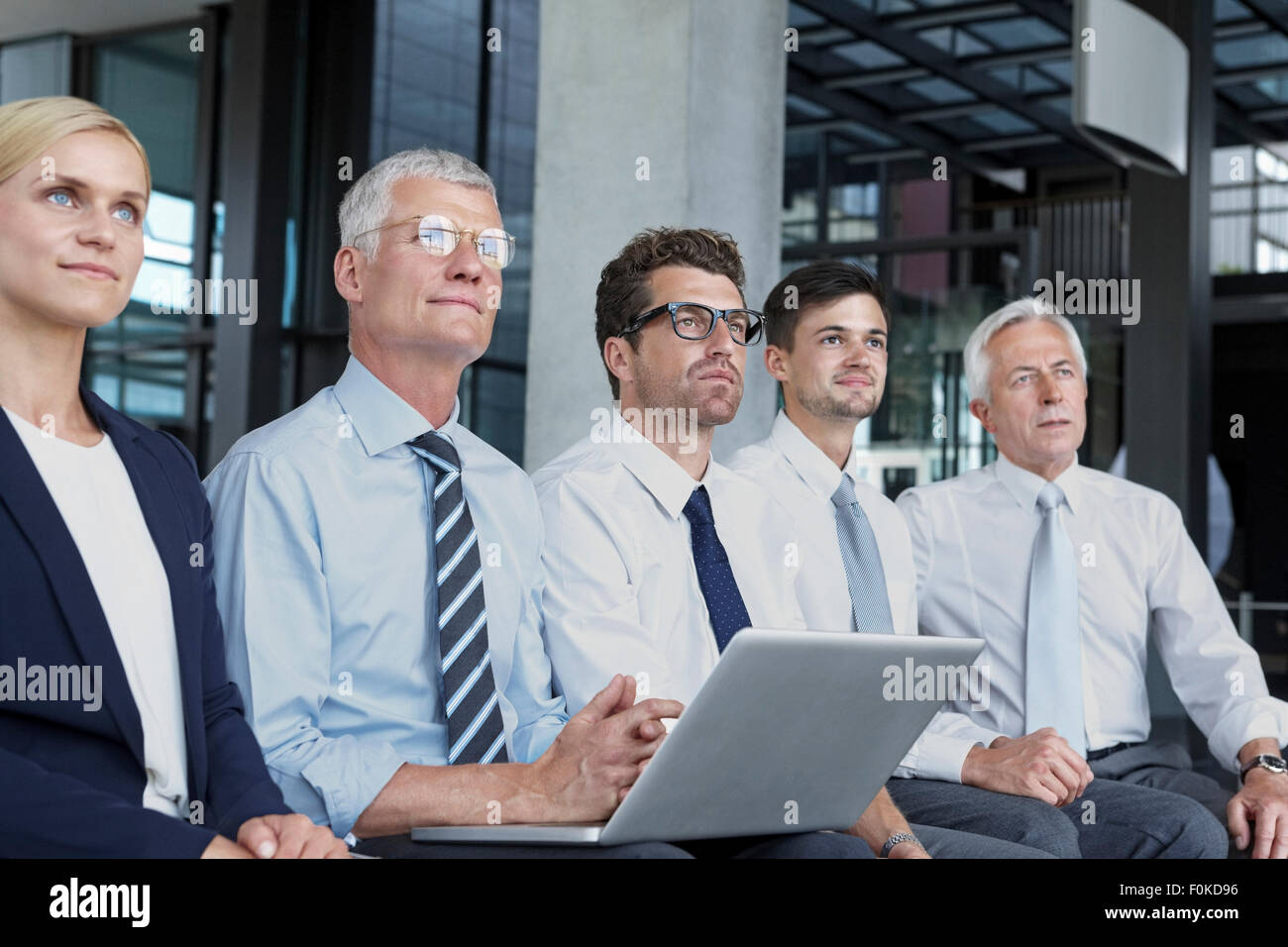 Group of businesspeople sitting in a row looking up - Stock Image
