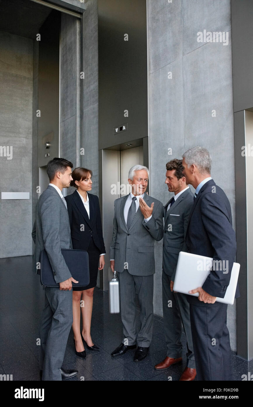 Group of businesspeople talking at an alevator in office - Stock Image