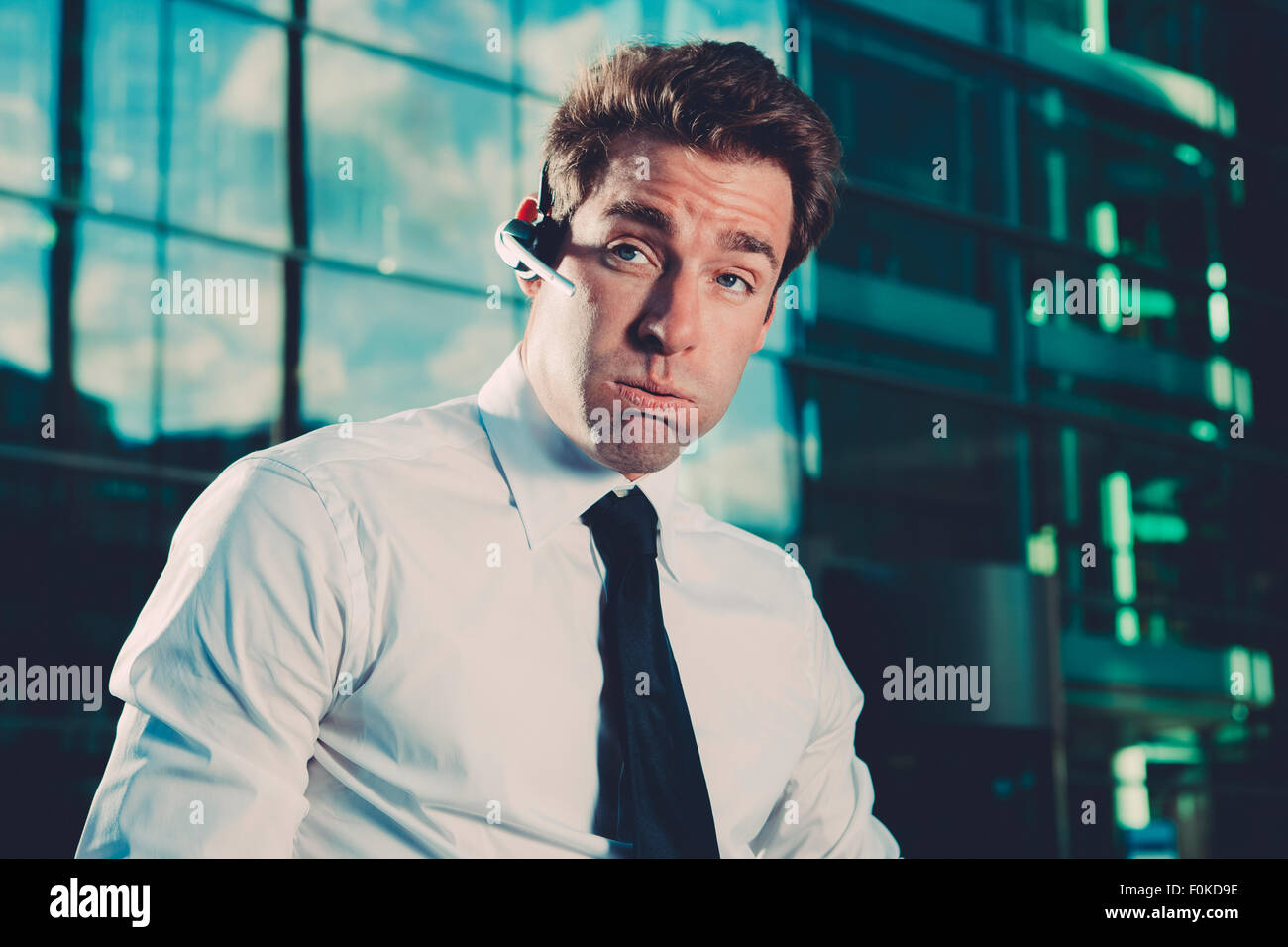 Businessman wearing bluetooth wireless device outside office building - Stock Image