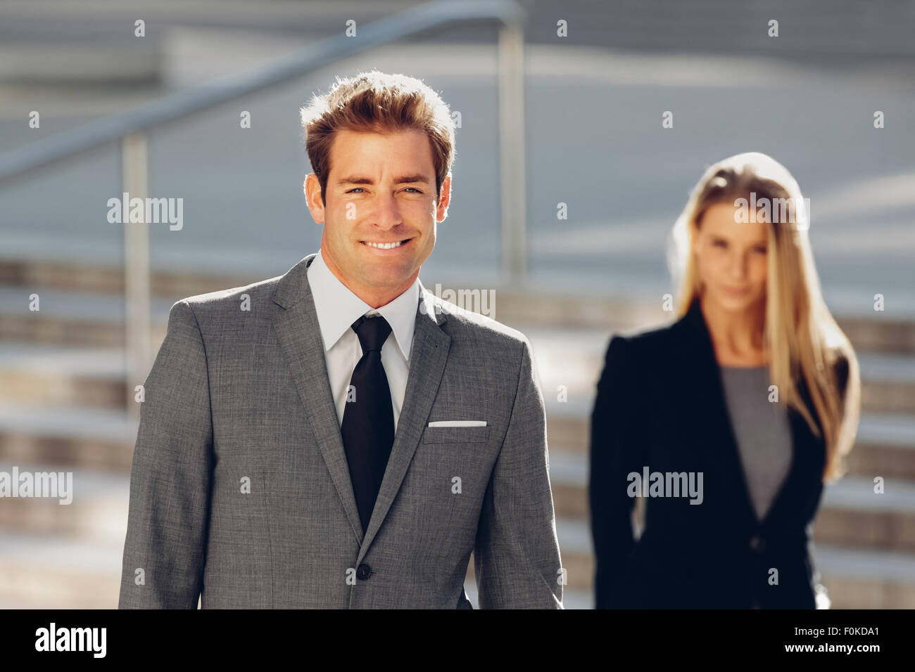 Smiling businessman with businesswoman in background - Stock Image