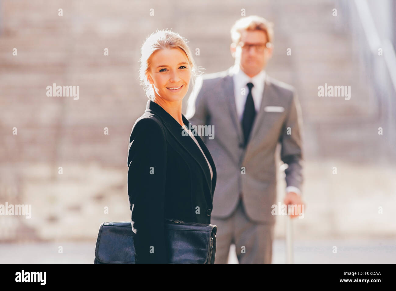 Smiling businesswoman with businessman in background - Stock Image