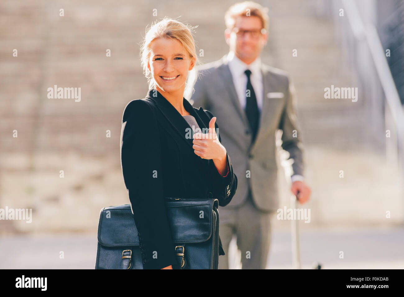 Optimistic businesswoman with businessman in background - Stock Image