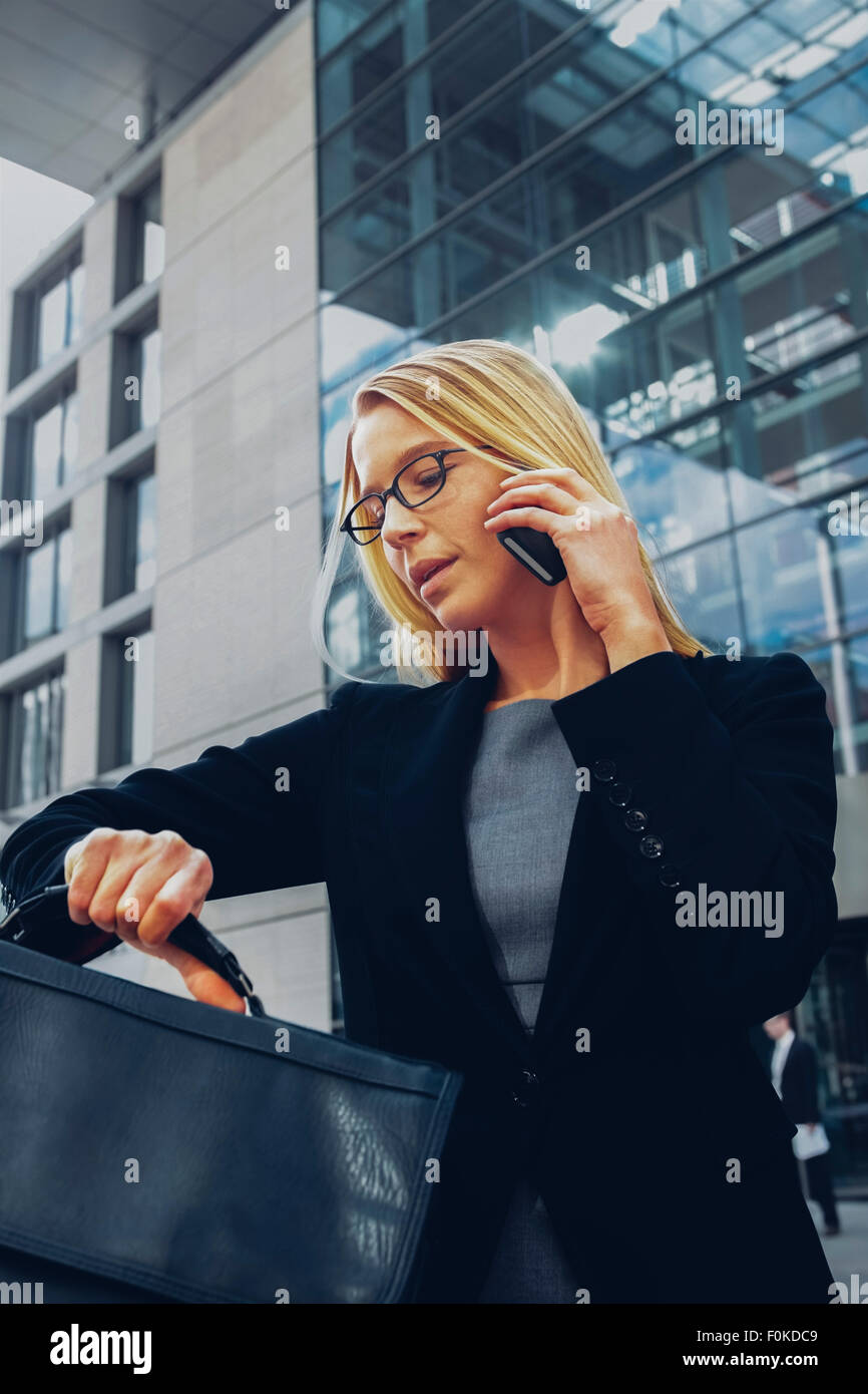 Businesswoman checking time while talking on cell phone outside office building - Stock Image