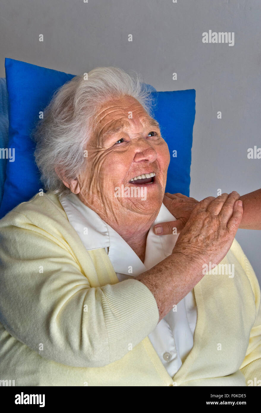 Happy laughing fulfilled elderly lady holds comforting arm of carer companion - Stock Image