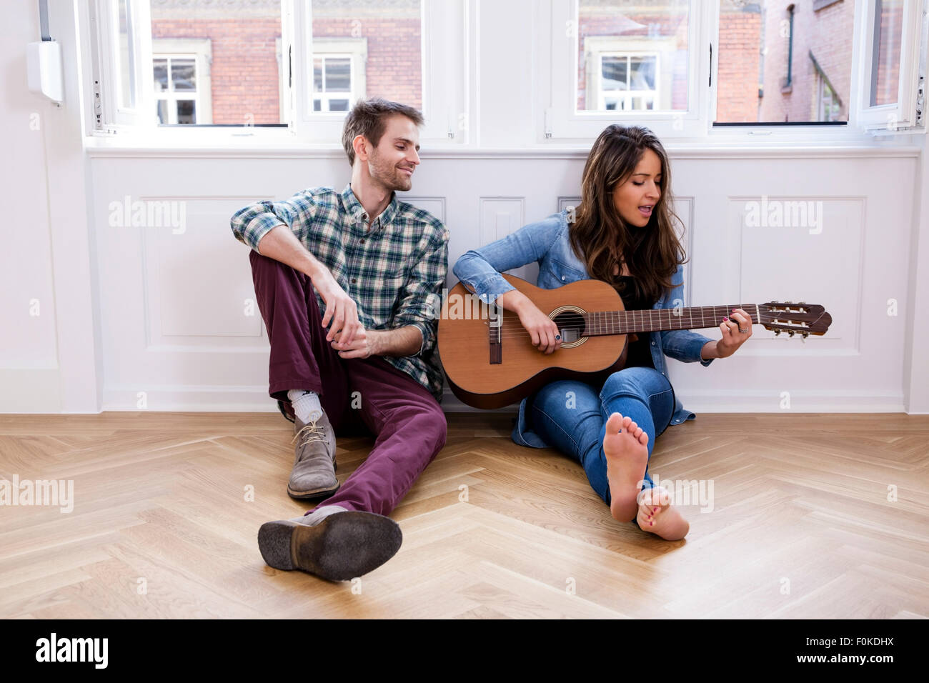 Young couple sitting on floor with woman playing guitar - Stock Image