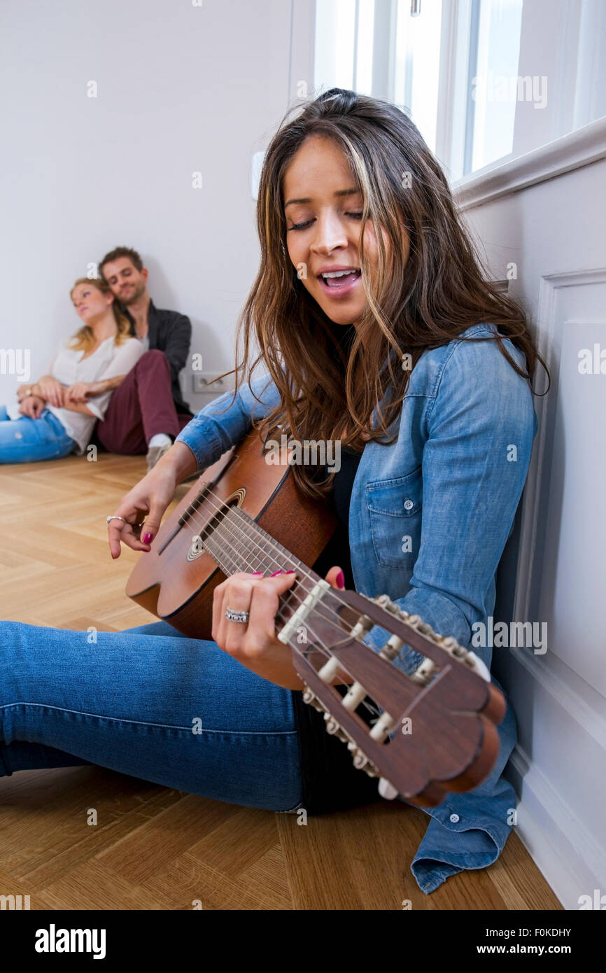 Young woman sitting on floor playing guitar with couple in background - Stock Image