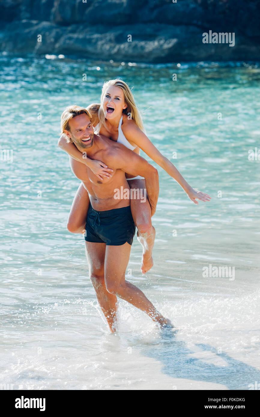 Spain, Majorca, man piggybacking his girlfriend at the sea - Stock Image
