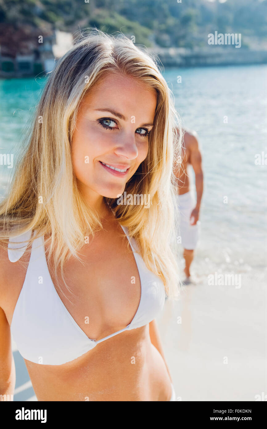 Spain, Majorca, smiling woman in bikini on the beach with man in background - Stock Image