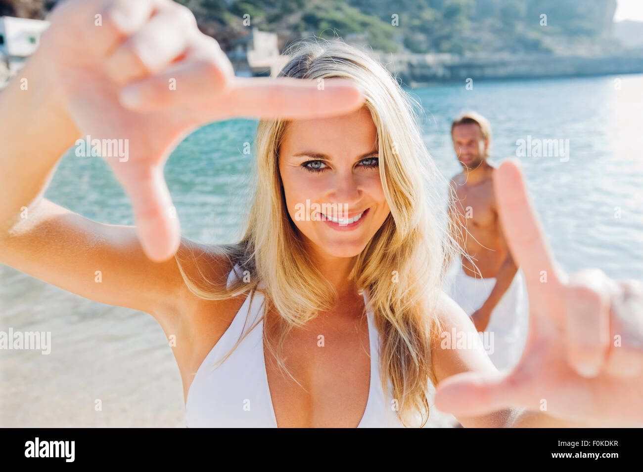 Spain, Majorca, smiling woman in bikini on the beach making a finger frame - Stock Image