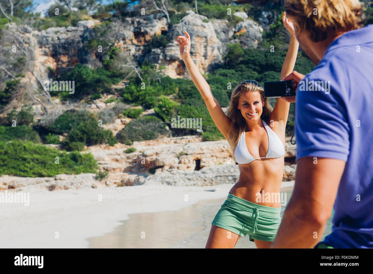 Spain, Majorca, woman on the beach posing for man with camera - Stock Image