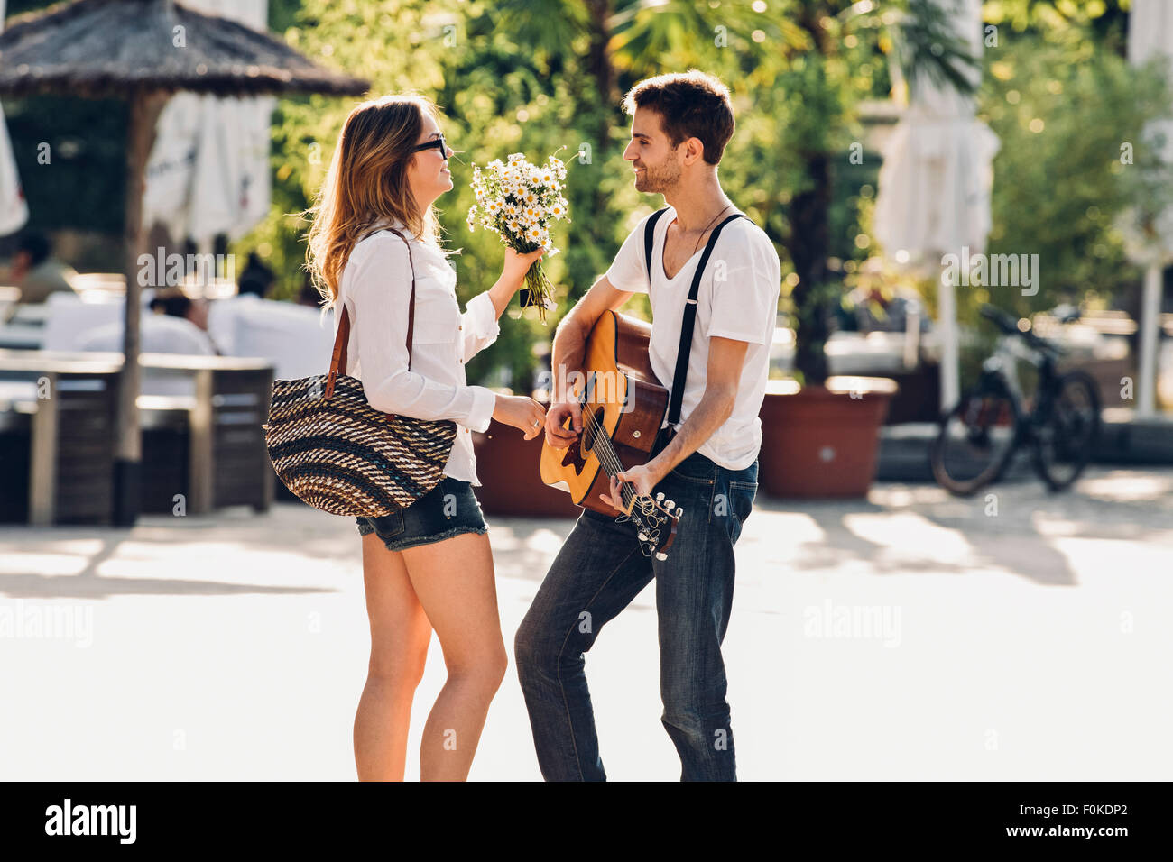 Loving young couple with guitar and bunch of flowers on the street - Stock Image