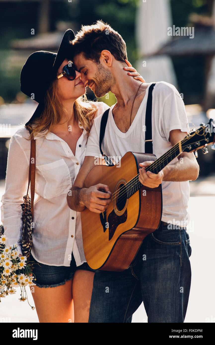 Loving young couple with guitar and bunch of flowers - Stock Image