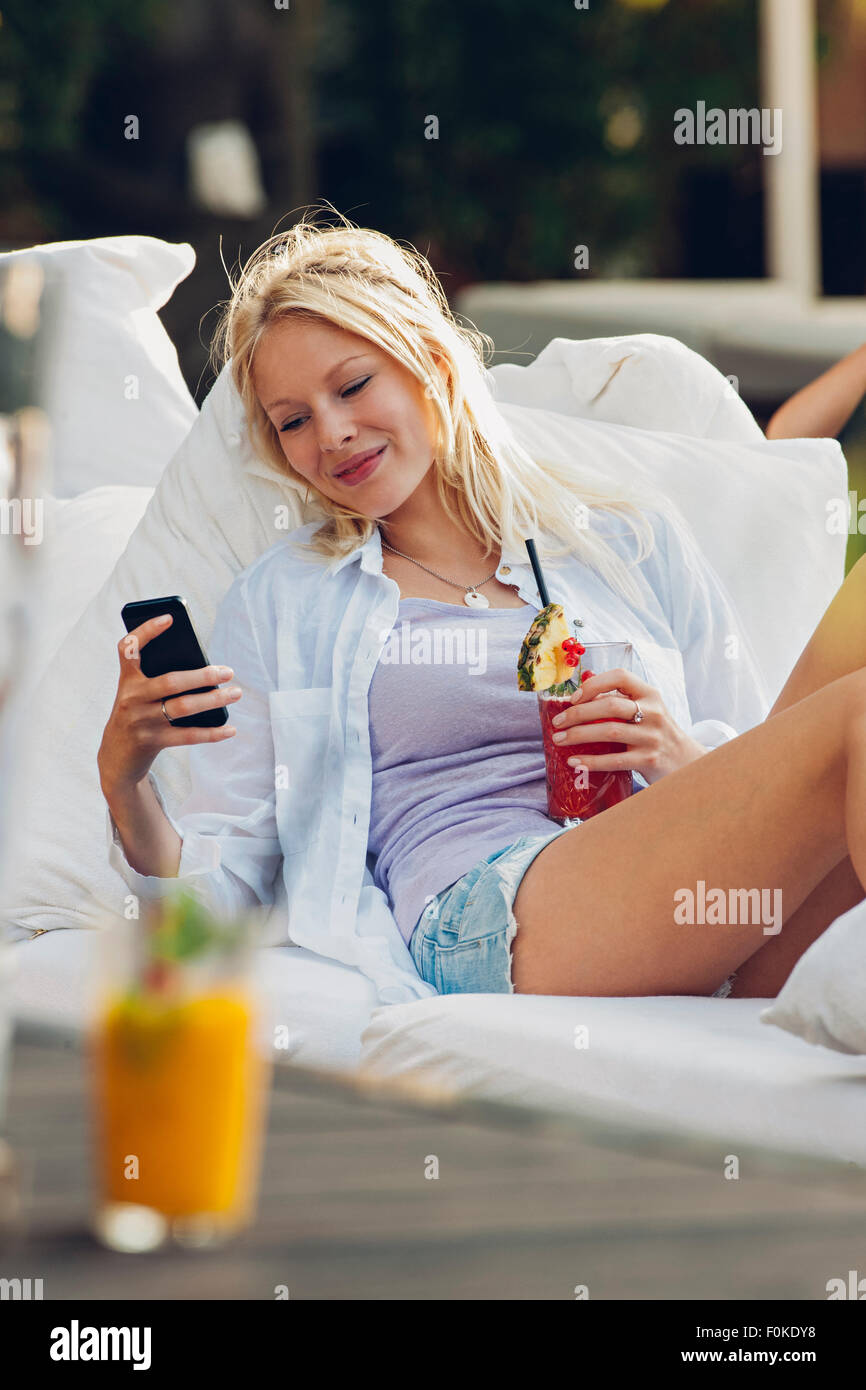 Young woman relaxing in a lounge bar looking at cell phone - Stock Image
