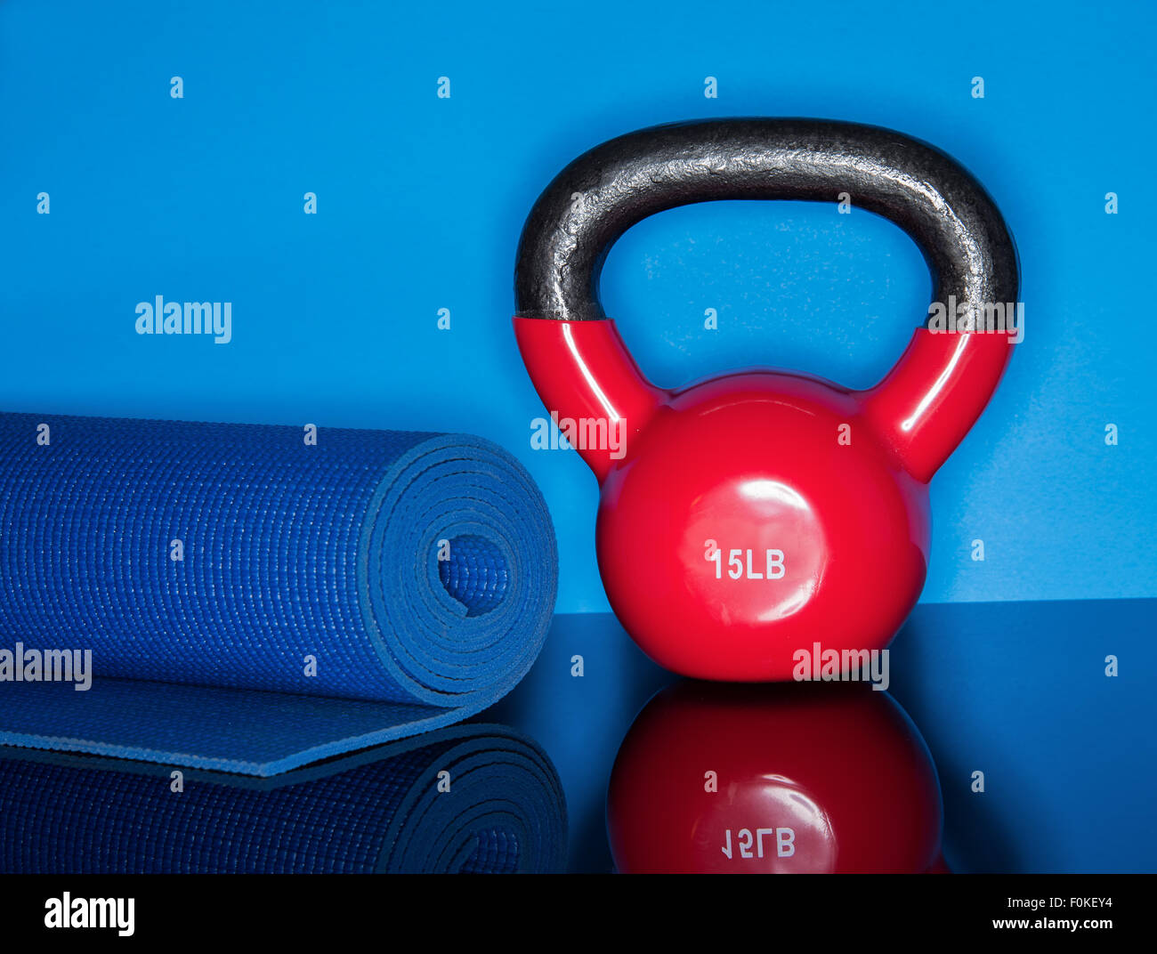 Red Kettle ball on blue background with mat roll - Stock Image