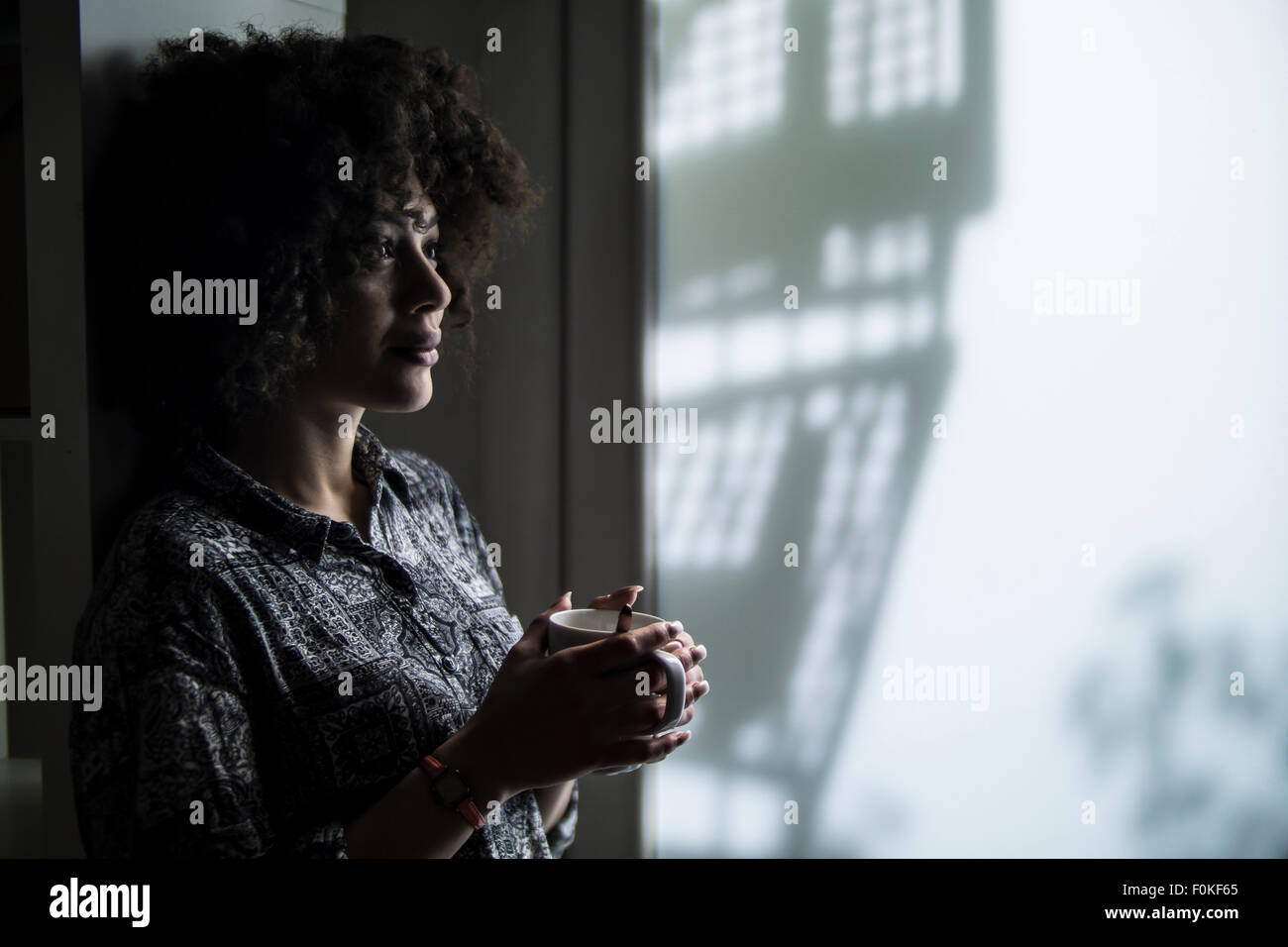 Dark-haired young woman thinking - Stock Image