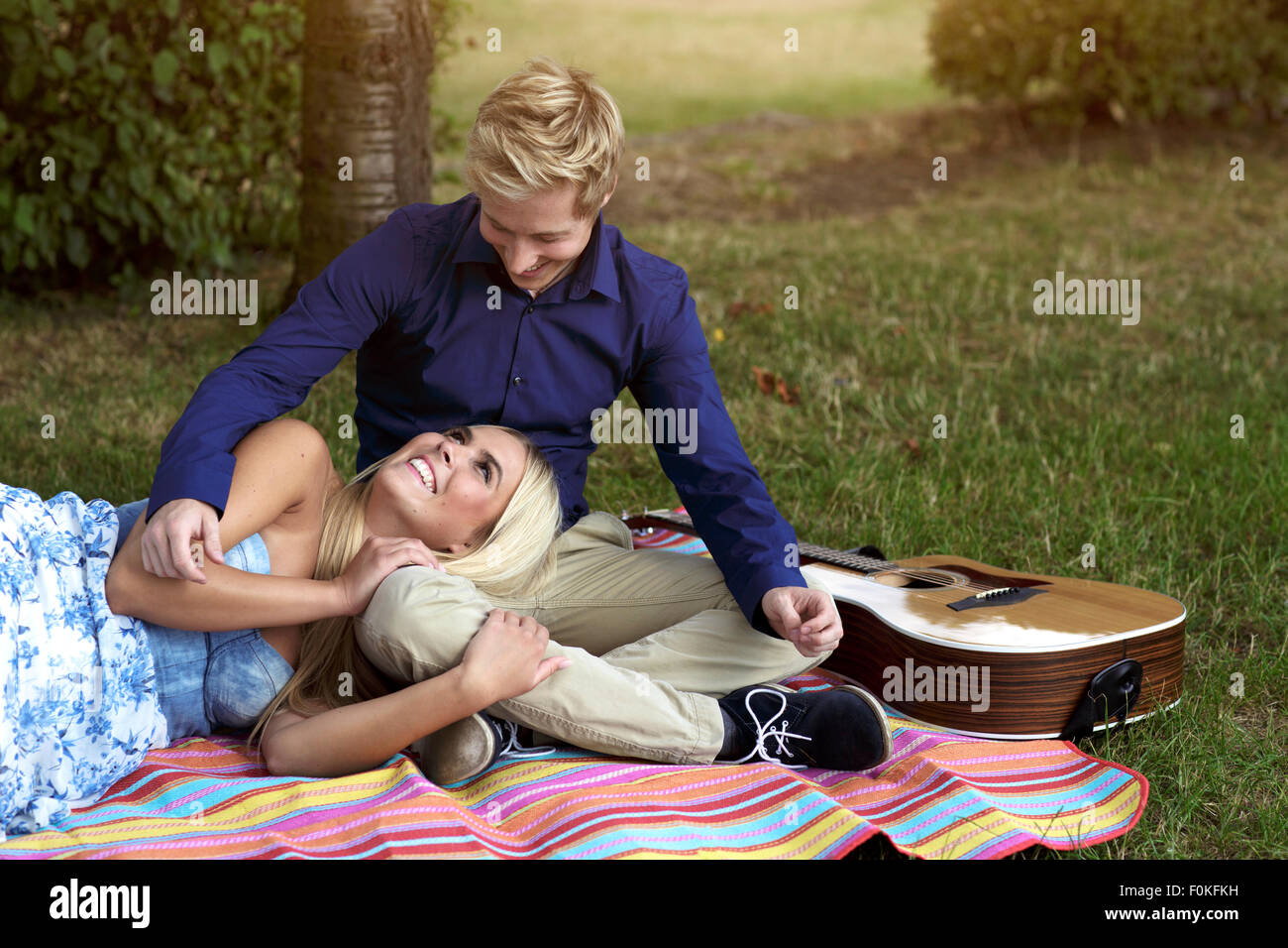 Happy young couple with guitar on blanket in park - Stock Image