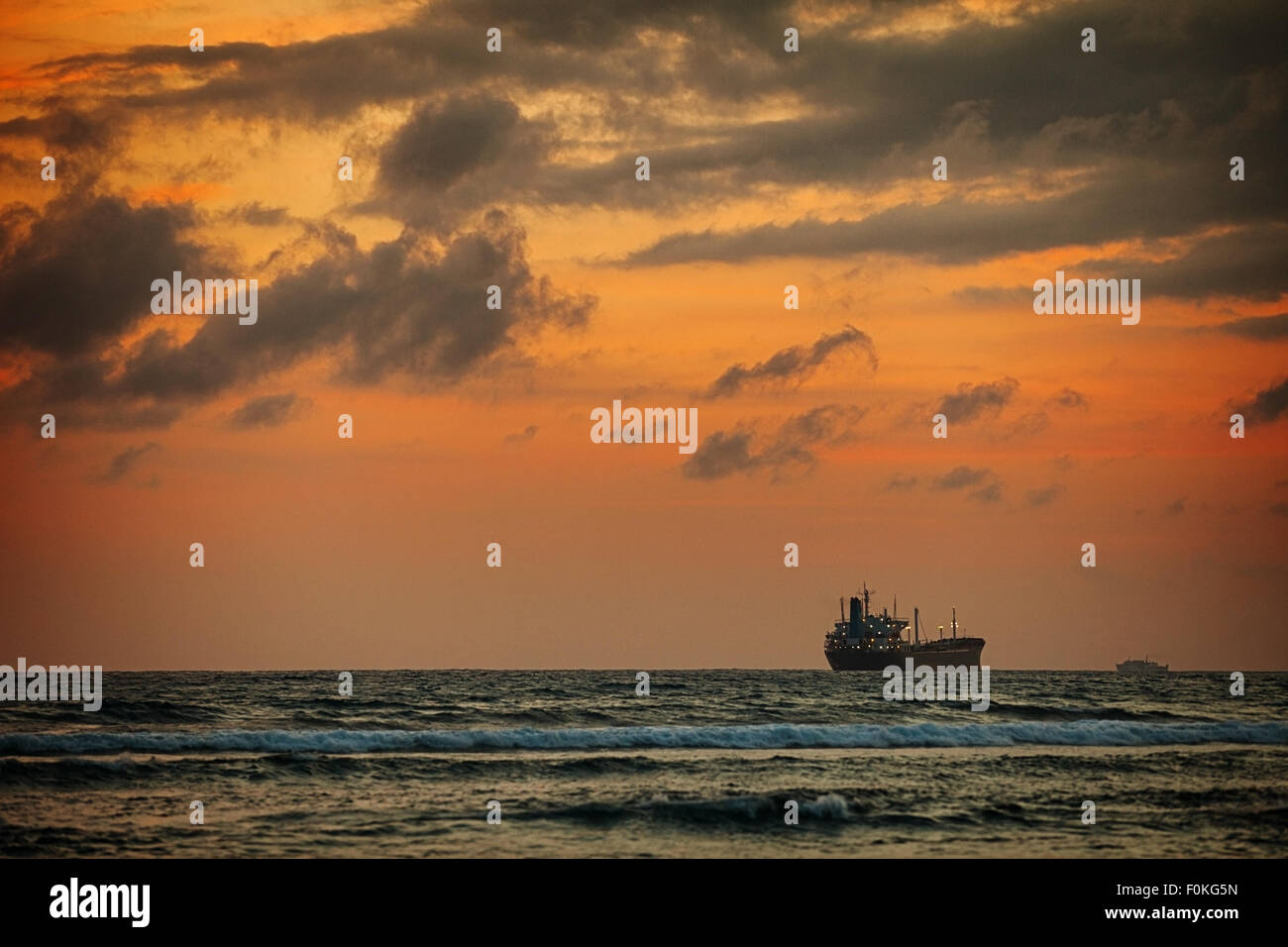 Enormous tanker ship, passing in the distance, along the horizon on this tropical sea at sunset. - Stock Image