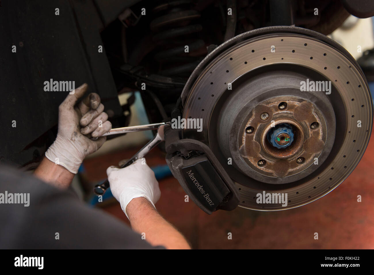 A car mechanic fits new brake pads to a car in a car garage during an MOT. - Stock Image