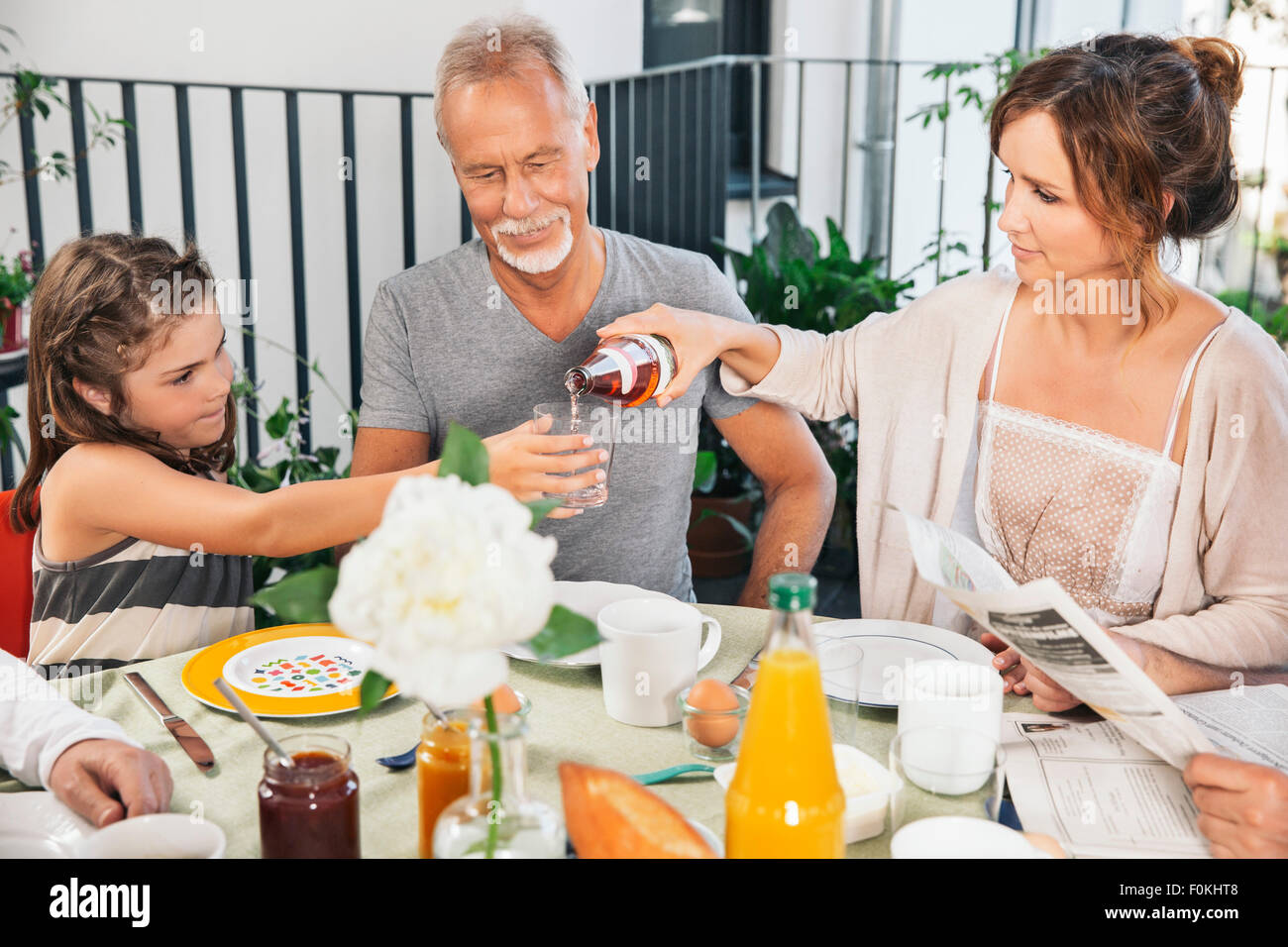 Three generations of family sitting at a large breakfast table on balcony - Stock Image